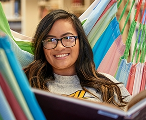 Female student reading book in colorful hammock in library