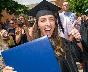 Happy female graduate with diploma in one hand and giving a thumbs up with her other hand