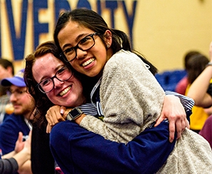 Two current student volunteers hugging during Celebration event for incoming students