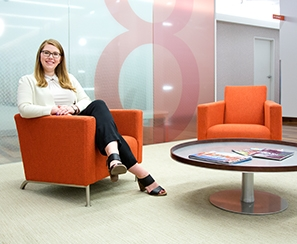Graduate student photographed in orange lobby chair at her place of employment
