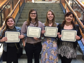 four girls holding diplomas
