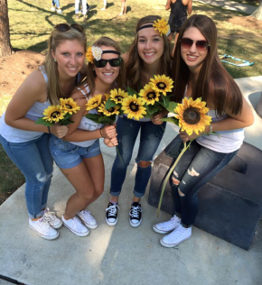 four girls holding sunflowers
