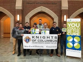 "Group of students holding up ""Knights of Columbus"" sign"