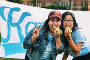 two girls eating hot dogs