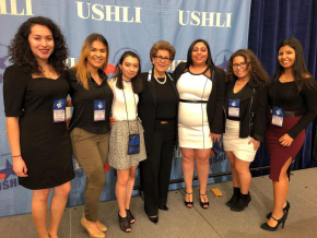 group of women sitting in front of a ushli sign