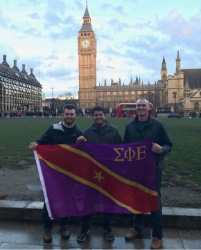 three men holding flag in front of the big ben