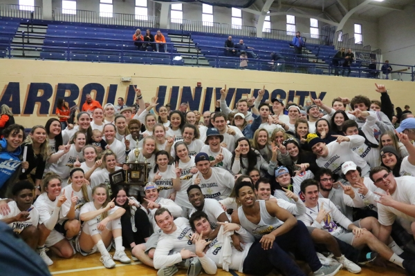 The women's basketball team celebrates their championship with fans.