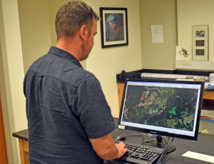 Watling stands in his lab at a computer and analyzes mapping data