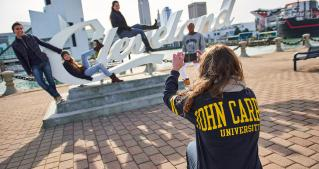 student taking photo of students on Cleveland sign