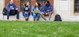 Four JCU students sitting of a curb