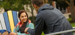 Female and male student talking while sitting in campus Adirondack chairs