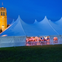Photo of the big Reunion tent at night with tower in the background