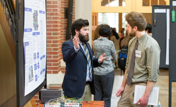 Brad Doughty (left) discusses his senior project at the Celebration of Scholarship poster session.