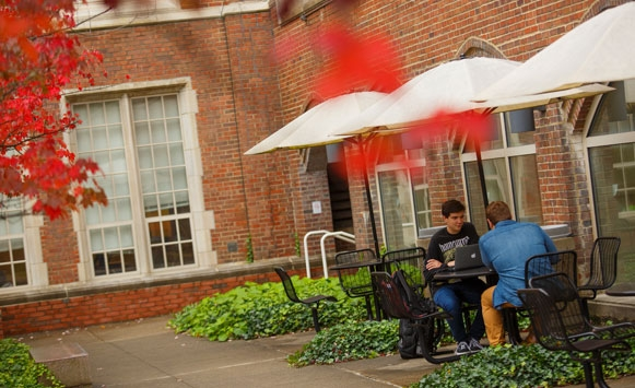Two male students studying outside at a table in the courtyard in the fall