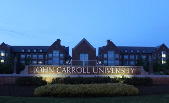 Picture of the front of campus with the John Carroll University sign and Dolan Science Center in the background at dusk