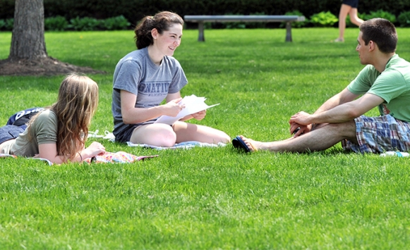 Three students studying on quad in spring