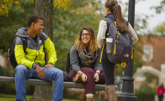 One male and two female students talking on a bench near the quad in the fall