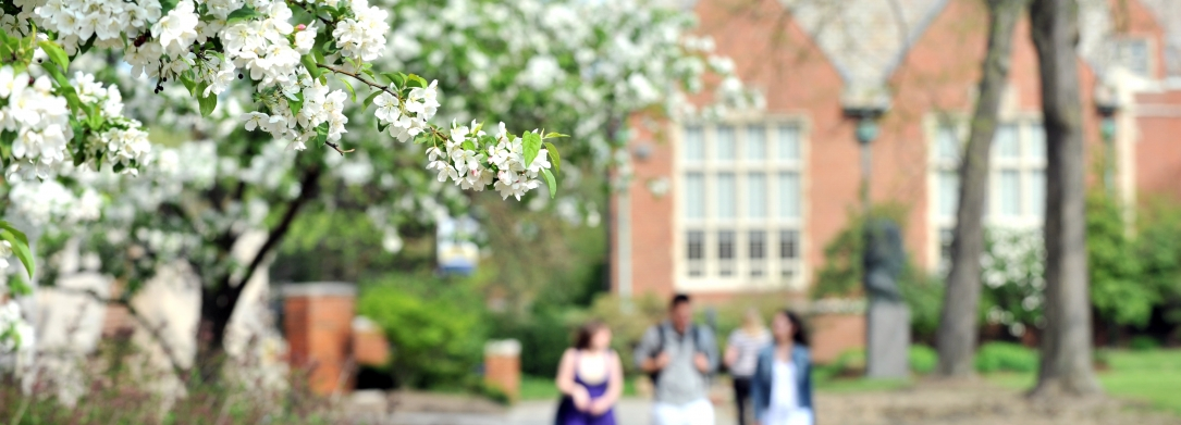 Group of students walking in front of the Administration Building with Rodman Hall in the background in the spring