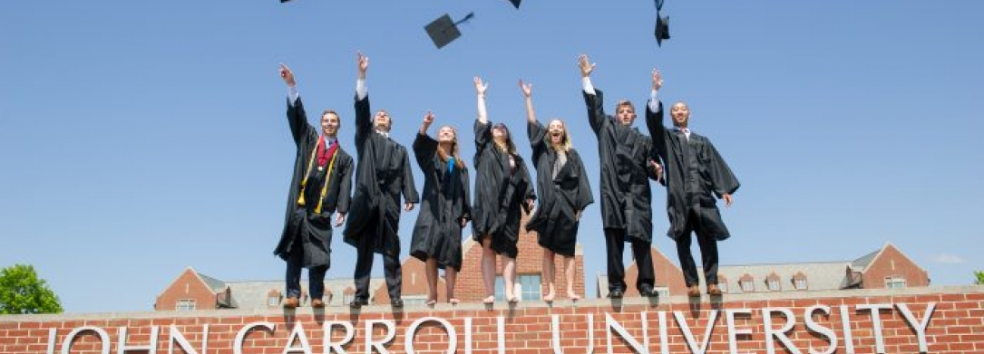 Picture of JCU celebrating graduation by throwing their caps in the air