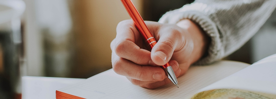 Hand holding a pen and writing in a notebook