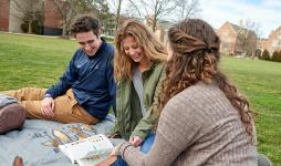 group pf students looking at book on quad