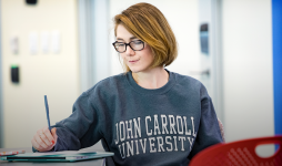Female student wearing JCU sweatshirt sits in a classroom and writes.