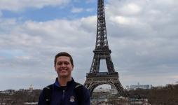 JCU student stands in front of the Eiffel Tower in Paris.