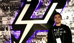 Brenan Betro stands in front of the San Antonio Spurs logo.