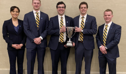 John Carroll CFA Challenge team members hold a trophy after winning their local competition.