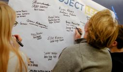 High School Juniors sign their name on a board at the Project Lead Summit