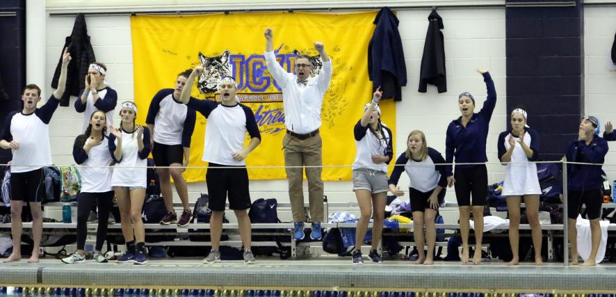 Mark Fino and his swimmers celebrate on the deck as JCU wins a race