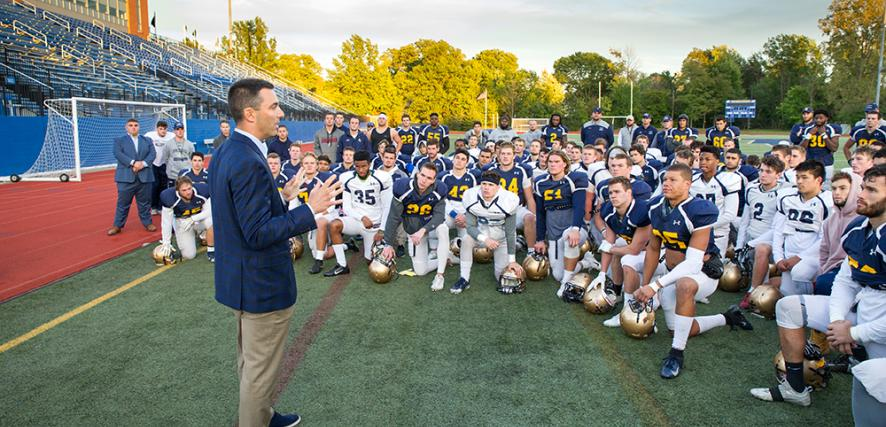Tom Telesco stands on Wasmer Field and addresses the football team.