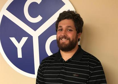 Vince Minniti stands in front of a CYO logo