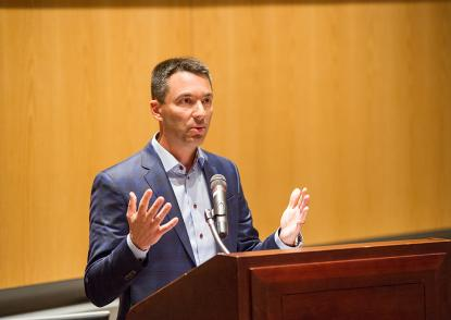 Tom Telesco stands at a podium and gestures during his lecture.