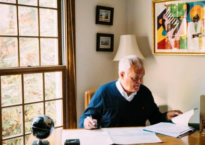 Bill O'Rourke sits at the desk in his home office