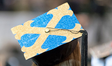 girl wearing graduation cap with JCU botany cross, viewed from back