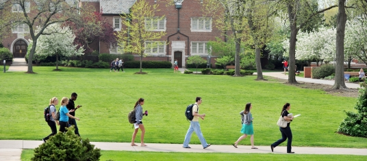 Students walking across campus on a spring day